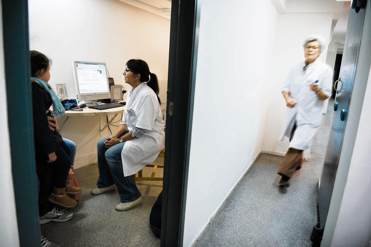 Dokter A. Stol-Jappie in de spreekkamer met een ziek kind met haar ouders.