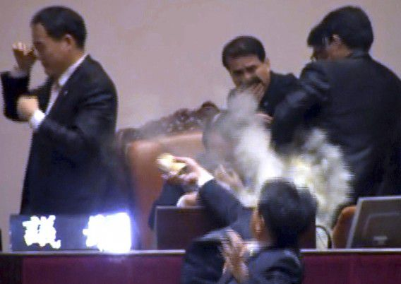 Lawmaker Kim Sun-dong (bottom) of the Democratic Labour Party detonates a tear gas canister towards the chairman's seat at the National Assembly, to try to stop the ruling Grand National Party's move to ratify a bill on a free trade agreement with the United States, in Seoul in this still image taken from video November 22, 2011. South Korea's ruling conservatives rammed a controversial free trade deal with the United States through parliament on Tuesday as legislators scuffled and one opposition MP let off a tear gas device, briefly clearing the chamber. REUTERS/Yonhap (SOUTH KOREA - Tags: POLITICS CIVIL UNREST BUSINESS TPX IMAGES OF THE DAY) NO SALES. NO ARCHIVES. FOR EDITORIAL USE ONLY. NOT FOR SALE FOR MARKETING OR ADVERTISING CAMPAIGNS. THIS IMAGE HAS BEEN SUPPLIED BY A THIRD PARTY. IT IS DISTRIBUTED, EXACTLY AS RECEIVED BY REUTERS, AS A SERVICE TO CLIENTS. SOUTH KOREA OUT. NO COMMERCIAL OR EDITORIAL SALES IN SOUTH KOREA