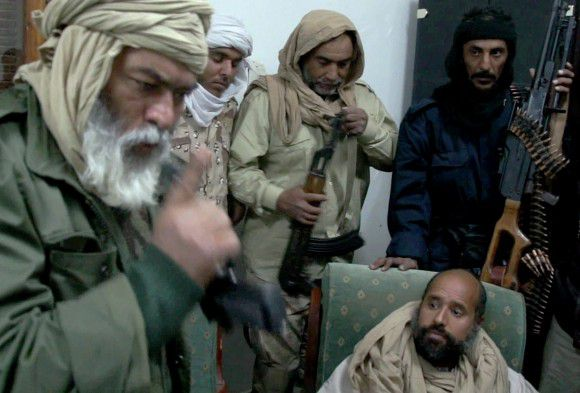 In this image taken from video made available Tuesday, Nov. 22, 2011, Moammar Gadhafi's son Seif al-Islam, below right, is surrounded by Libyan revolutionary captors shortly after his capture on Saturday, Nov. 19, 2011, at a safe house in the town of Zintan, Libya. The video shows Seif al-Islam arguing with his captors and admonishing them, saying that Libya's regions that were united in revolution will turn against each other in the near future and rip the country apart. (AP Photo/APTN) TV OUT