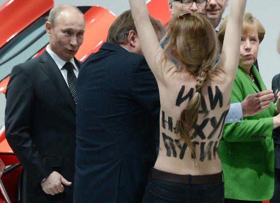 Poetin kijkt geschrokken/geïnteresseerd naar een van de blote demonstranten