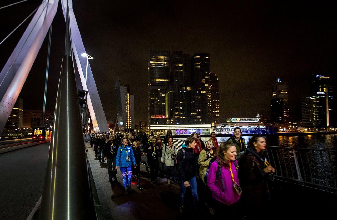 Wandelaars lopen in 2016 op de Erasmusbrug aan het begin van de Nacht van de Vluchteling op de route naar Den Haag. De opbrengst van de sponsorloop is voor noodhulp aan vluchtelingen en ontheemden wereldwijd.
