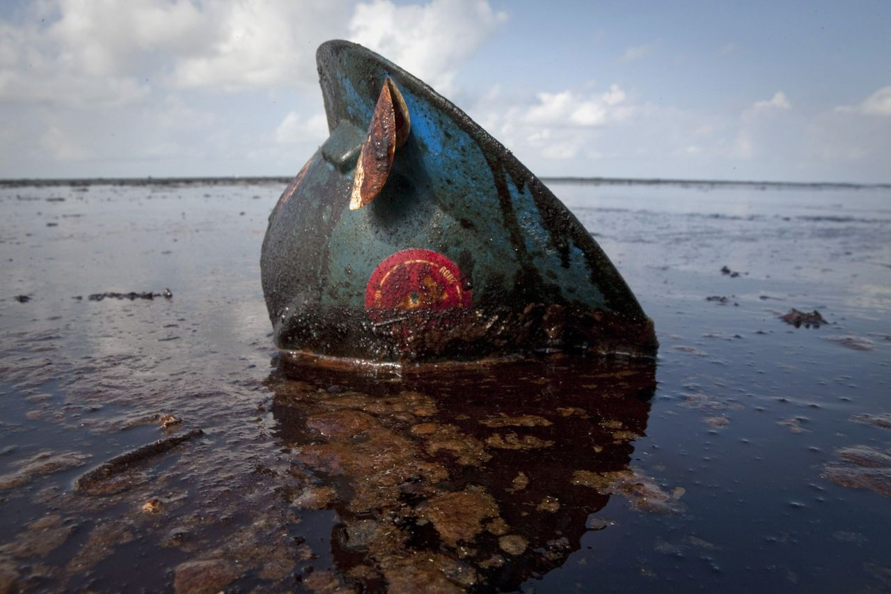 A hard hat from an oil worker lies in oil from the Deepwater Horizon oil spill on East Grand Terre Island, Louisiana in this June 8, 2010 file photo. REUTERS/Lee Celano/Files To match Special Report BP/COSTS (UNITED STATES - Tags: DISASTER ENERGY ENVIRONMENT BUSINESS)