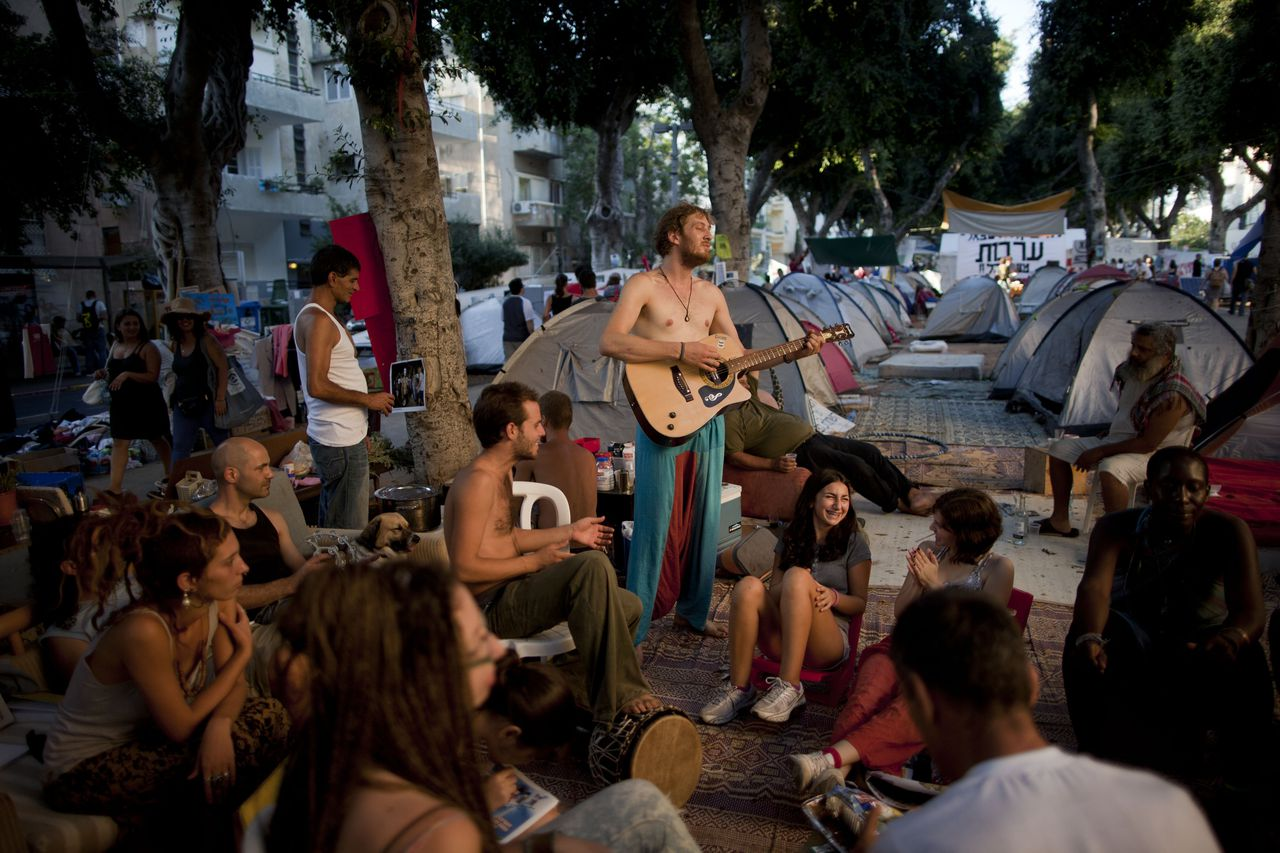 In this photo taken on Thursday, Aug. 4, 2011, Israeli protesters play music in a protest tent encampment against the costs of living in Israel, in Tel Aviv, Israel. Israel on Sunday, Aug. 7, 2011, formed a panel of government ministers and some of the country's leading economic experts to draw up a plan to reduce the soaring cost of living, marking a new effort to defuse demonstrations over prices that drew over a quarter-million people onto the streets the night before. (AP Photo/Oded Balilty)