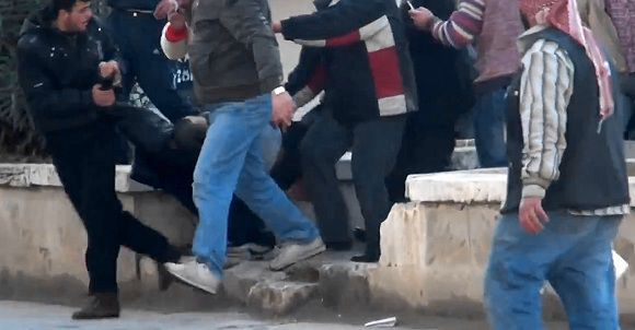 Caption: This image made from amateur video and made available by Shaam News Network dated Friday, Dec. 30, 2011, purports to show a wounded protester carried away by others in Idlib, Syria. Syria's two largest opposition groups signed an agreement on setting up a democracy after President Bashar Assad's regime falls, opposition figures said Saturday, Dec. 31, 2011. (AP Photo/Shaam News Network via APTN) TV OUT. THE ASSOCIATED PRESS CANNOT INDEPENDENTLY VERIFY THE CONTENT, DATE, LOCATION OR AUTHENTICITY OF THIS MATERIAL. TV OUT