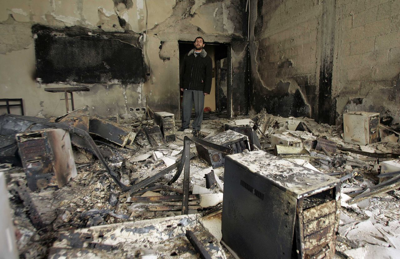 A Palestinian looks at a burnt building inside the Islamic University after it was attacked in Gaza February 3, 2007. Fighting between rival Palestinian factions escalated across Gaza on Friday, killing at least 17 people, as Hamas Islamists overran compounds used by President Mahmoud Abbas' forces and two universities were set ablaze. REUTERS/Mohammed Salem (GAZA)
