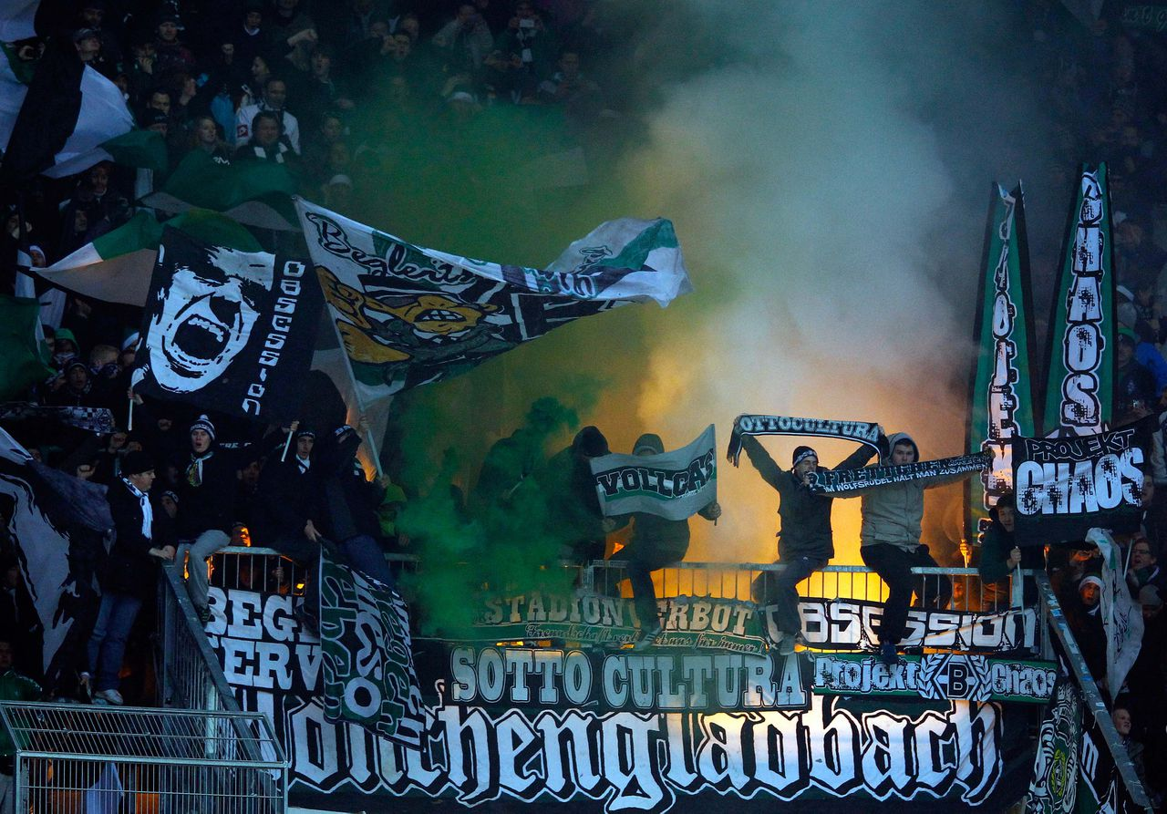 Borussia Moenchengladbach supporters light flares before their German Bundesliga first division soccer match in Augsburg December 10, 2011. REUTERS/Michael Dalder (GERMANY - Tags: SPORT SOCCER) DFL LIMITS USE OF IMAGES ON THE INTERNET TO 15 PICTURES DURING THE MATCH AND, PROHIBITS MOBILE (MMS) USE DURING AND UP TO 2 HOURS POST MATCH. FOR MORE INFORMATION CONTACT DFL