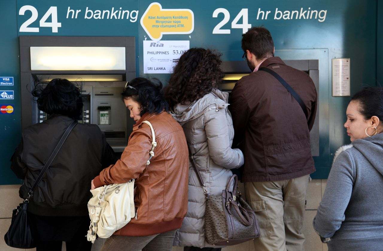 People withdraw money from a cash-point machine in the Cypriot capital Nicosia on March 17, 2013. The Cyprus government postponed a planned emergency session of parliament on Sunday to debate a controversial EU bailout, state media said, as the scale of opposition to its terms became clear. AFP PHOTO BARBARA LABORDE