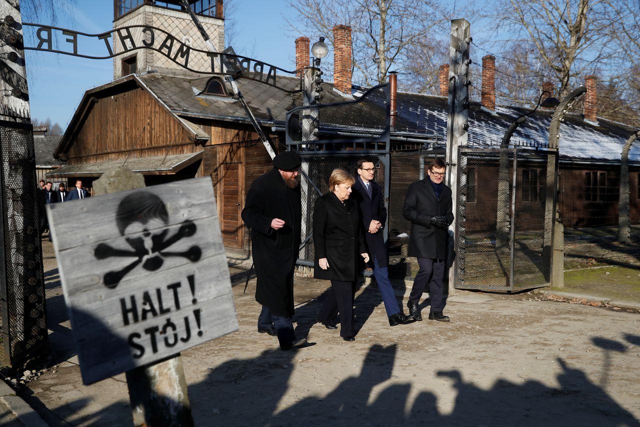 """Angela Merkel, de Poolse premier Mateusz Morawiecki en museumdirecteur Piotr Cywinski lopen onder de poort door met daarop de tekst """"Arbeit macht frei""""."""