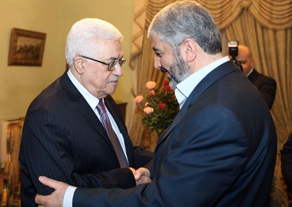 "Caption: A hand out picture provided by the Hamas press office shows Palestinian president Mahmud Abbas (L) shaking hands with the exiled leader of the Palestinian Islamist movement Hamas, Khaled Meshaal (R) during their meeting in Cairo on December 21, 2011. Palestinian factions, led by the former rivals Hamas and Fatah meeting in Cairo are mulling ways to reactivate their national parliament, which has been paralysed since 2007 following the split between the West Bank and Gaza. AFP PHOTO/RESTRICTED TO EDITORIAL USE - MANDATORY CREDIT ""AFP PHOTO /HAMAS PRESS OFFICE /MOHAMMED AL-HAMS "" - NO MARKETING NO ADVERTISING CAMPAIGNS - DISTRIBUTED AS A SERVICE TO CLIENTS"