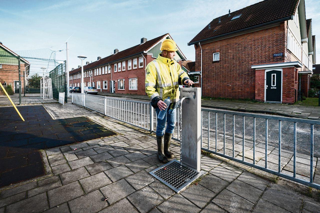 Een watertappunt aan de Texelweg in de wijk Tuindorp Buiksloot in Amsterdam-Noord. Veel bewoners tappen hier hun drinkwater.