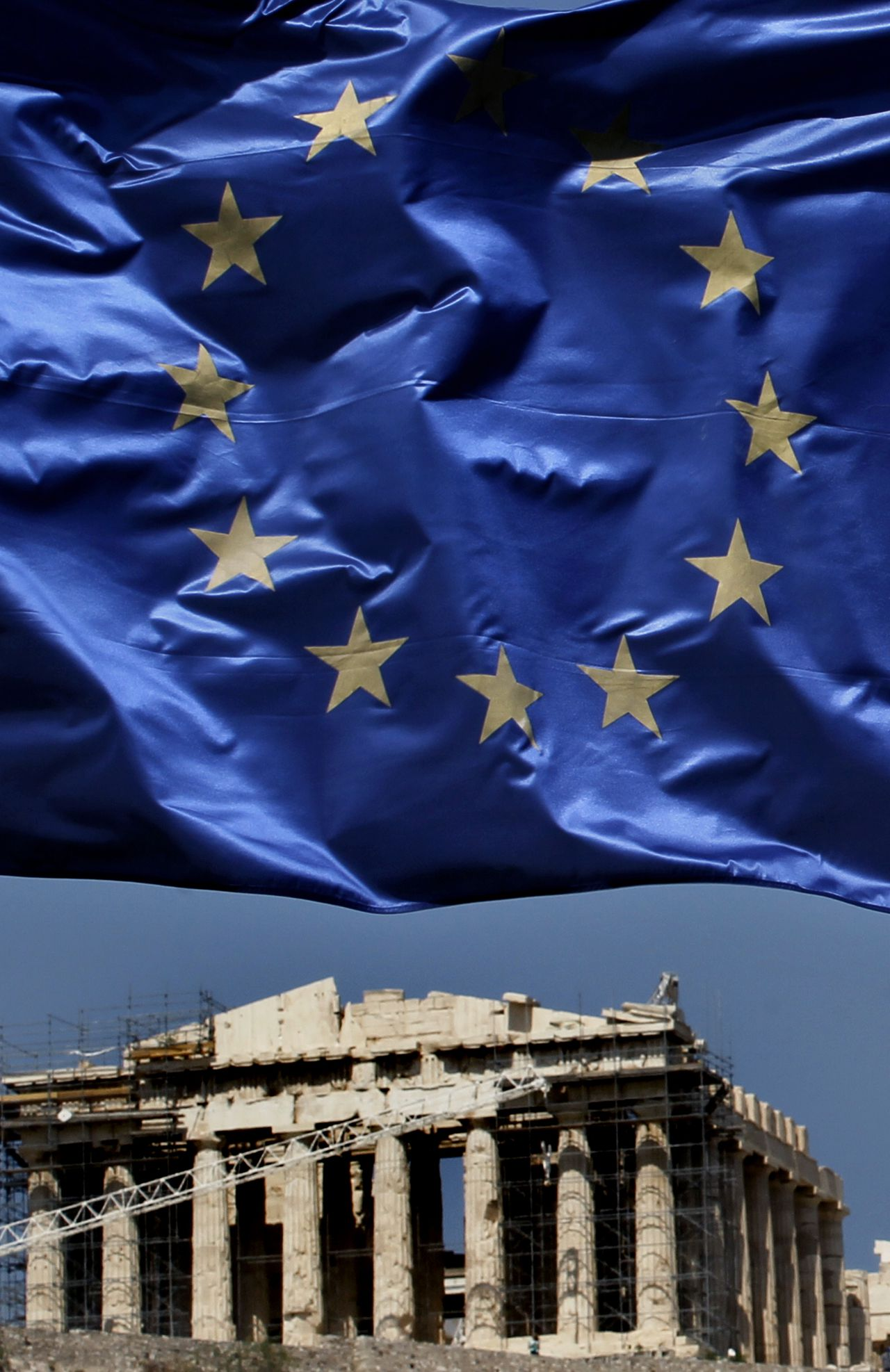 A European Union flag waves above the ancient Parthenon temple, at the Acropolis Hill, in Athens on Monday, July 11, 2011.Greece's Socialist government on Monday named a five-member committee to head a euro50 billion ($71.2 billion) privatization program aimed at easing the country's euro340 billion ($484.2 billion) national debt. (AP Photo/Petros Giannakouris)