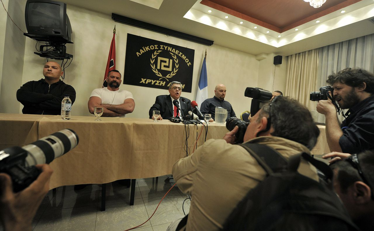 Political leader of the Greek far-right party Chryssi Avghi (Golden Dawn), Nikolaos Michaloliakos (C) speaks during a press conference at an hotel in Athens on May 6, 2012, after the first results of the Greek general elections. The Greek neo-Nazi Golden Dawn party will enter parliament for the first time in nearly 40 years, exit polls showed on Sunday as ballots closed in an early election that could derail the country's reforms. AFP PHOTO / LOUISA GOULIAMAKI