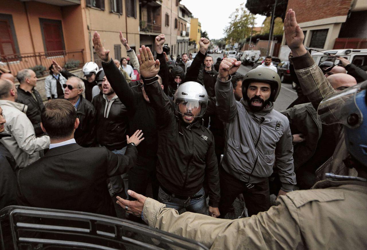 Italiaanse neonazi's brengen de Hitlergroet in Albano Laziale, waar gistermiddag een begrafenismis voor oud-SS'er Priebke was gepland. De mis werd opgeschort.