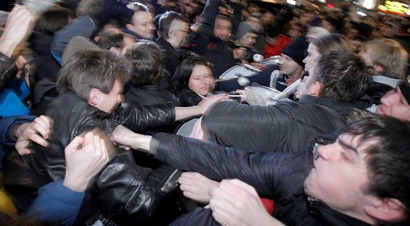 Caption: Opposition activists, left, and members of pro-Kremlin youth movements scuffle during demonstrations in Triumphal Square in Moscow, Russia, Tuesday, Dec. 6, 2011. Police clashed Tuesday on a central Moscow square with demonstrators trying to hold a second day of protests against alleged vote fraud in Russia's parliamentary elections. (AP Photo/Ivan Sekretarev)