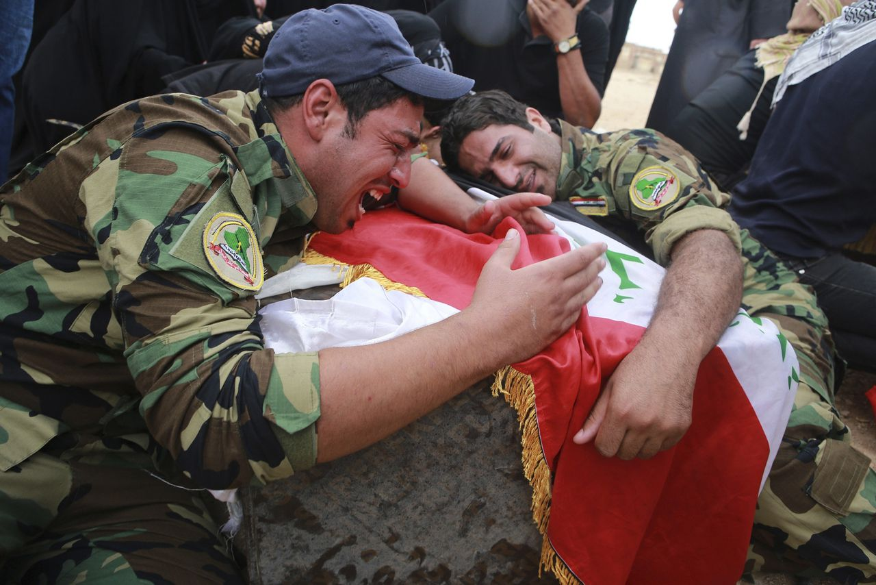 Mourners grieve on the coffins of two members of Asaib Ahl al-Haq killed in clashes with the Free Syrian Army, during a funeral in Najaf, 160km (100 miles) south of Baghdad, May 3, 2013. The two Iraqi men, members of Asaib Ahl al-Haq, were killed in clashes with the Free Syrian Army at the Sayeda Zainab area in Damascus. REUTERS/Ahmad Mousa (IRAQ - Tags: CIVIL UNREST POLITICS)