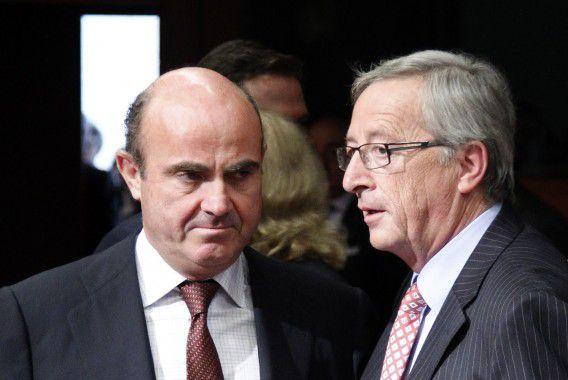 De Spaanse minister van Economische Zaken Luis de Guindos en de Luxemburgse premier en eurogroepvoorzitter Jean-Claude Juncker gisteravond in Brussel. Foto Reuters / Francois Lenoir