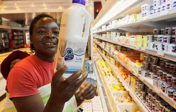 Caption: A woman holds a pint of fresh milk from Alpha Omega Dairy, owned by Zimbabwean First Lady Grace Mugabe, in a supermarket in Harare July 5, 2012. Alpha Omega Dairy this week started distribution of dairy products to stores around Zimbabwe. Last year global food giant Nestle was forced to stop buying milk from the Mugabe farm after protests from human rights groups. REUTERS/Philimon Bulawayo (ZIMBABWE - Tags: AGRICULTURE POLITICS FOOD BUSINESS)