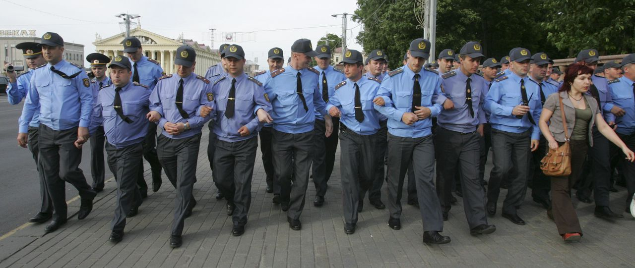 """Politie blokkeert een protest in Minsk. Duizend mensen betoogden woensdag tegen de regering. Foto Reuters Belarussian policemen block the pavement in central Minsk, June 15, 2011. About one thousand people gathered in the Belarussian capital to take part in a flash mob """"Revolution via social network"""" to demonstrate their desire for changes in the economic and political life of the country, but they were dispersed by the police. REUTERS/Vladimir Nikolsky (BELARUS - Tags: POLITICS CIVIL UNREST)"""