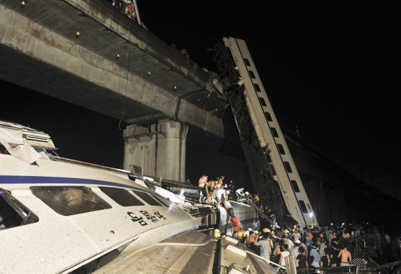 RETRANSMISSION FOR ALTERNATIVE CROP - Emergency workers and people work to help passengers from the wreckage of train after two carriages from a high-speed train derailed and fell off a bridge in Wenzhou in east China's Zhejiang province Saturday July 23, 2011. A Chinese news agency says there is no immediate word on casualties.(AP Photo) CHINA OUT