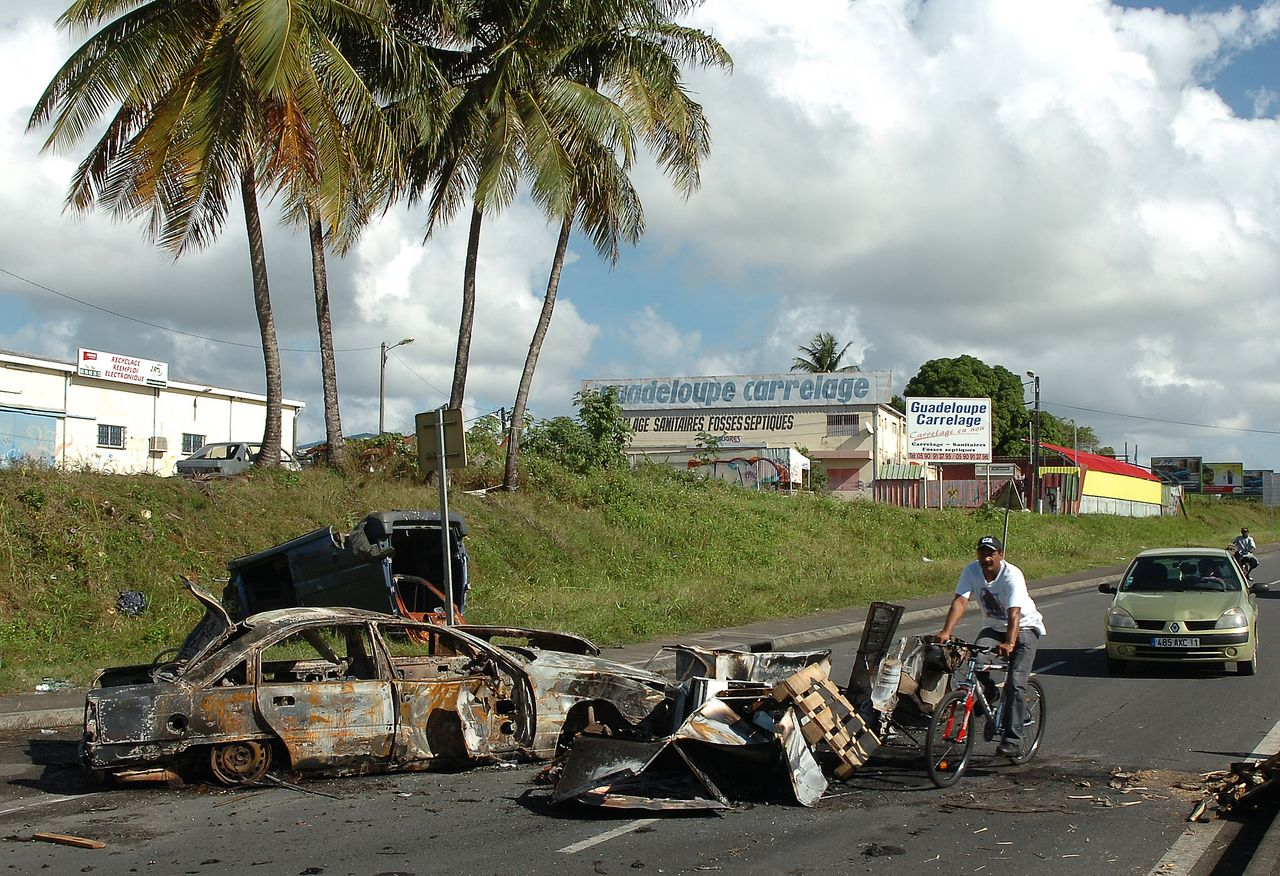 Een uitgebrande auto en puin blokkeren een weg op het Franse eiland Guadeloupe. Begin dit jaar kwam het tot rellen tijdens protesten tegen de hoge prijzen. Foto Reuters Wrecked cars partially block a road in Abymes near Pointe-a-Pitre after a second night of violence February 18, 2009. Armed youths shot dead a union member and injured several police on the French Caribbean island of Guadeloupe overnight in an escalation of violence after weeks of protest over economic conditions. REUTERS/Gilles Petit (GUADELOUPE)