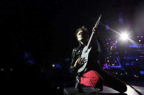 De Britse gitarist en zanger Matthew Bellamy van rockband Muse buigt door de knieën tijdens een optreden in het Dragao Stadium in Porto, Portugal, in 2013.