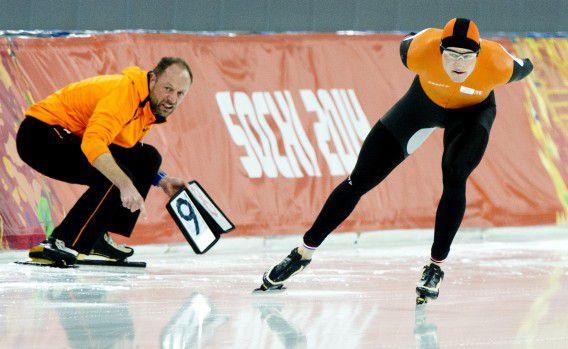 Sven Kramer tijdens de olympische 10.000 meter in Sotsji. Coach Gerard Kemkers staat met het rondebord.