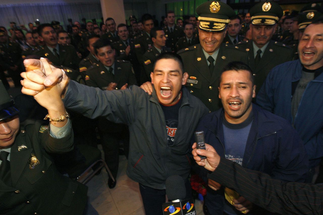 De Colombiaanse politieagenten John Jairo Duran (midden) en Armando Castellanos (rechts) vieren hun bevrijding van de FARC in een politieclub in Bogota. Foto Reuters Colombian policemen John Jairo Duran (C), Armando Castellanos (2nd R) and Julio Buitrago (R), rescued by army troops, celebrate as they arrive at a police club in Bogota July 3, 2008. French-Colombian politician Ingrid Betancourt, three Americans and 11 other hostages held for years in jungle captivity were rescued on Wednesday from leftist guerrillas by Colombian troops posing as aid. REUTERS/Jorge Silva (COLOMBIA)