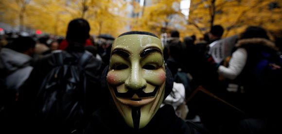 "Caption: A protester, wearing a Guy Fawkes mask, stands among the Occupy Wall Street demonstrators during what organizers call a ""Day of Action"" in New York, November 17, 2011. New York police on Thursday prevented protesters from shutting down Wall Street with an Occupy Wall Street rally that led to over 100 arrests but drew fewer than expected demonstrators. REUTERS/Brendan McDermid (UNITED STATES - Tags: BUSINESS CIVIL UNREST)"
