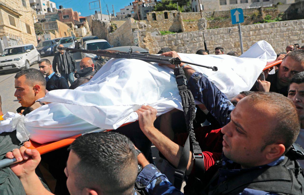 Het lichaam van een doodgeschoten Palestijnse agent wordt afgevoerd.