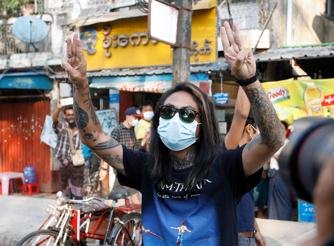 Een demonstrant in Yangon houdt drie vingers omhoog, een symbool van protest na de staatsgreep. Op het shirt de tekst A dramatic turn of events, naar een album van progressieve metalband Dream Theater.