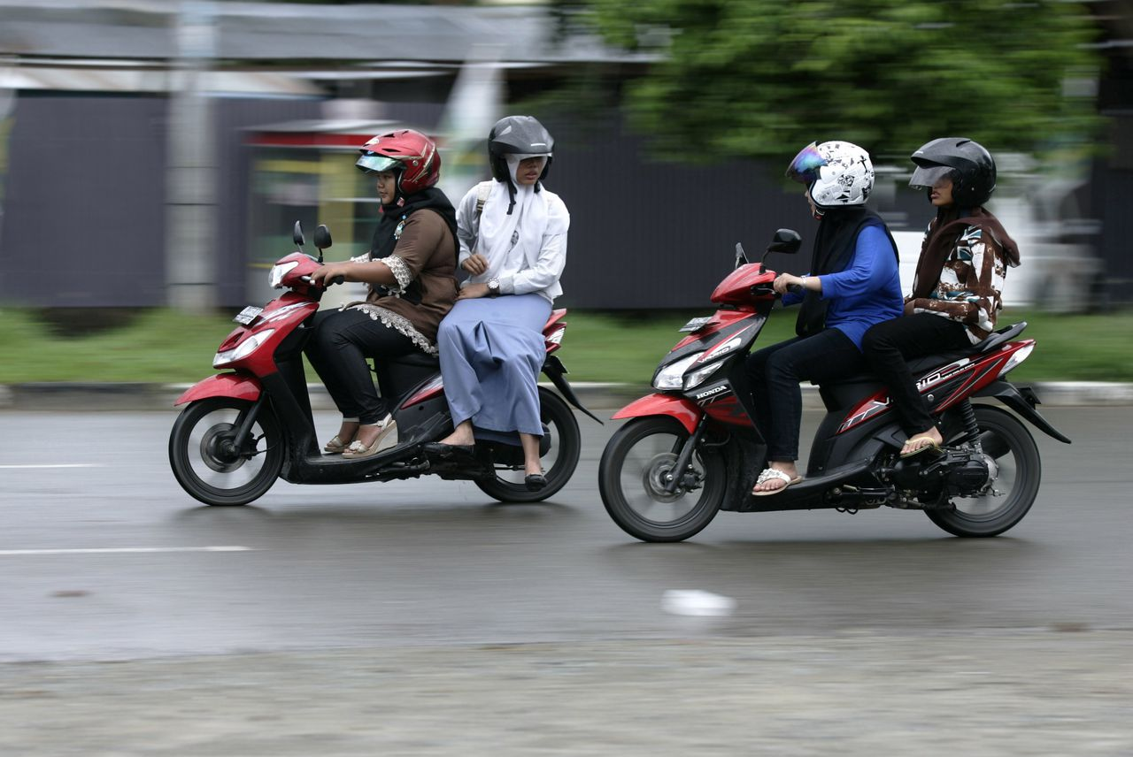 Acehnese women sit straddling on their motorcycles in Banda Aceh in Banda Aceh, Indonesia's Aceh province January 3, 2013. The administration of Lhokseumawe town, Aceh province, which is governed by Islamic Sharia law, is planning to issue a bylaw banning women from straddling motorcycles, arguing that the practice is improper for women, local media reported on Tuesday. REUTERS/Junaidi Hanafiah (INDONESIA - Tags: LAW TRANSPORT RELIGION)