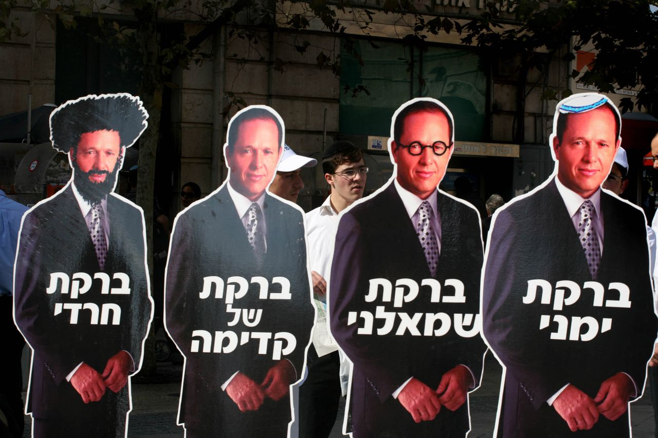 Nir Barkat zoals zijn tegenstanders hem zien Foto AFP Supporters of Jerusalem municipal elections candidate rabbi Meir Porush hold up placards showing his rival Nir Barkat , as a right-winger, as a left-winger, as a member of Kadima party and as an Ultra-Orthodox Jew on November 10, 2008 in downtown Jerusalem. Israel goes to the polls tomorrow for municipal elections which are enlivened this year by a mayoral race in Jerusalem that highlights the city's deep political and religious divisions. AFP PHOTO/GALI TIBBON