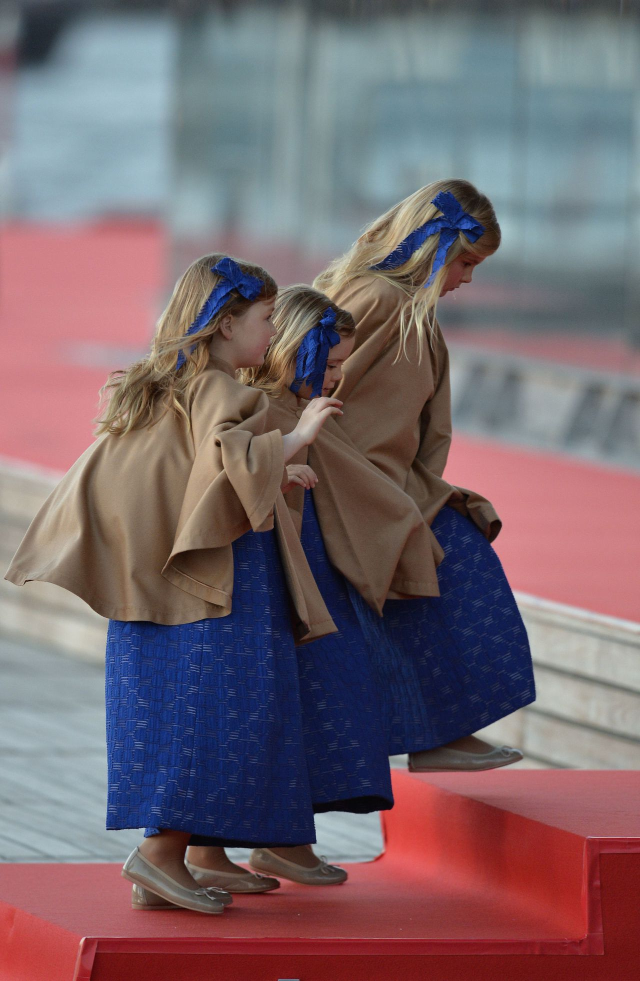 Catharina-Amalia, Princess of Orange (C) and Princesses Ariane and Alexia walk toward a boat on April 30, 2013 prior to take part in a water pageant on the river IJ in Amsterdam on the day of the new King's investiture AFP PHOTO / ODD ANDERSEN