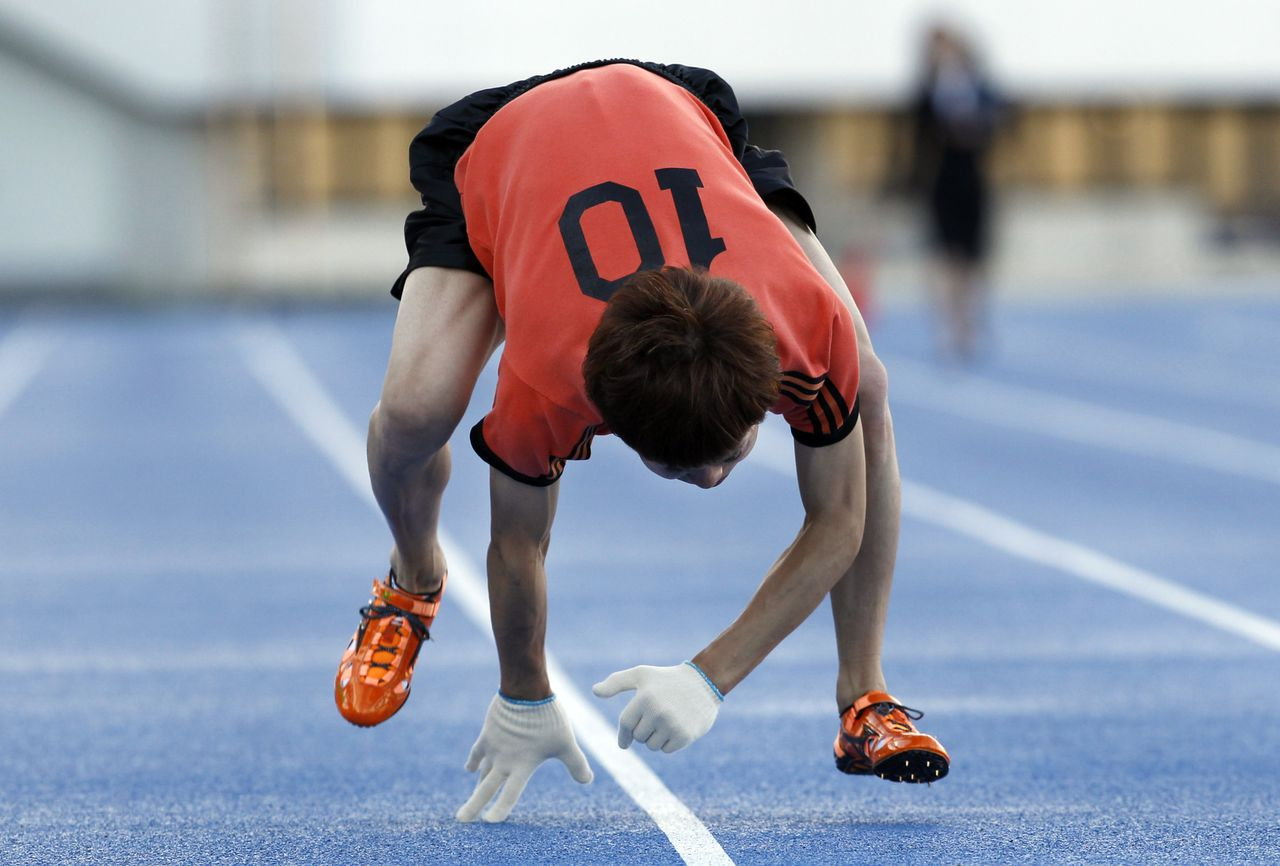 """Kenichi Ito runs on a race course on his way to setting the Guinness World Record for the fastest time to run 100 meters on all fours at Komazawa Olympic Park Stadium in Tokyo Thursday, Nov. 15, 2012. Known as """"Monkey Man,"""" Ito, 30, who has trained the four-legged style walking and running for nine years in his daily life by studying primates' movements through books, video and visiting the zoo frequently, ran in 17.47 seconds, 1.11 seconds faster than the time he set in 2008. (AP Photo/Koji Sasahara)"""