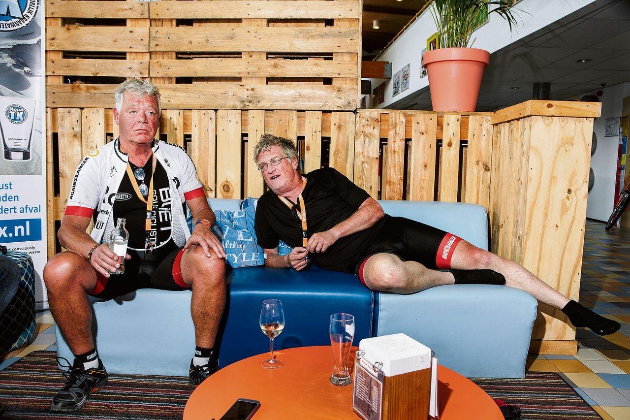 """Johnny Rep na zijn eigen wielerronde op Texel. Liggend zijn biograaf Mark van den Heuvel. """"Nou, ik heb het niet uitgefietst, maar het was wel mooi weer."""""""