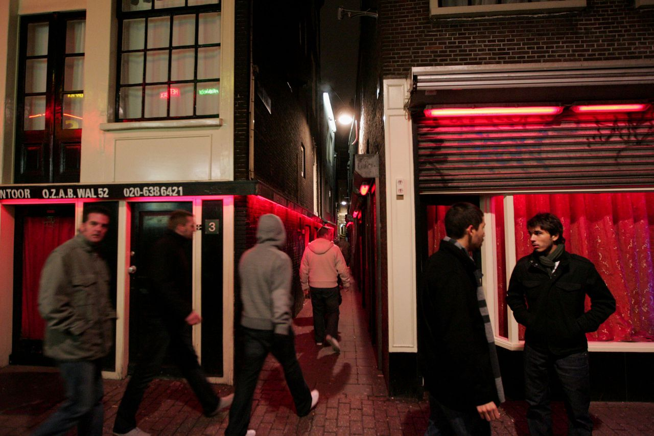 Bezoekers van de Amsterdamse Wallen, ook bekend als Red Light district. (Foto AFP) TO GO WITH AFP STORY BY MARIETTE LE ROUX (FILES)---A file picture taken on December 8, 2008 shows clients and tourists walk around Amsterdam's red-light district where prostitutes are exposed in shop windows. As the credit crunch keeps away sight-seers and business travellers, the owners of brothels, escort agencies and sex shops all grumble that those visitors who do still indulge in the pleasures of the flesh are increasingly tight-fisted. Eva, a 25-year-old prostitute in Amsterdam's red-light district, gestures angrily in the direction of a rival who has slashed her rates as the economic crisis emboldens sex tourists to haggle. AFP PHOTO/ANOEK DE GROOT