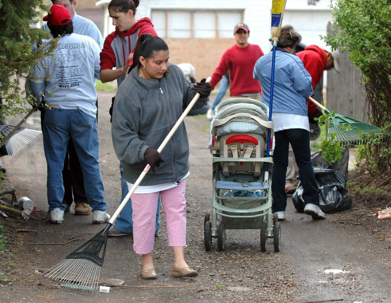 Mariela Tellez rakes an alley on South Bend's west side during an immigration day of action, Monday, May 1, 2006, in South Bend, Ind. The clean-up was part of actions taken by immigrants and their supporters who are expected to skip work and school and boycott businesses across the country Monday to protest proposed crackdowns on illegal immigration. (AP Photo/Joe Raymond) noodzakelijk werk dat de Amerikaan laat liggen gebeurt door illegalen. Straatvegen, kinderopvang, etc. Foto AP, bewerking fotostudio nrc.next