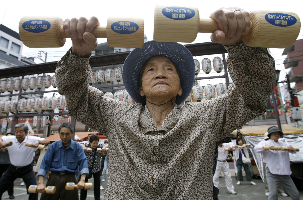 """An elderly woman exercises with wooden dumbbells during a health promotion event to mark Japan's """"Respect for the Aged Day"""" at a temple in Tokyo September 15, 2008. REUTERS/Toru Hanai (JAPAN)"""