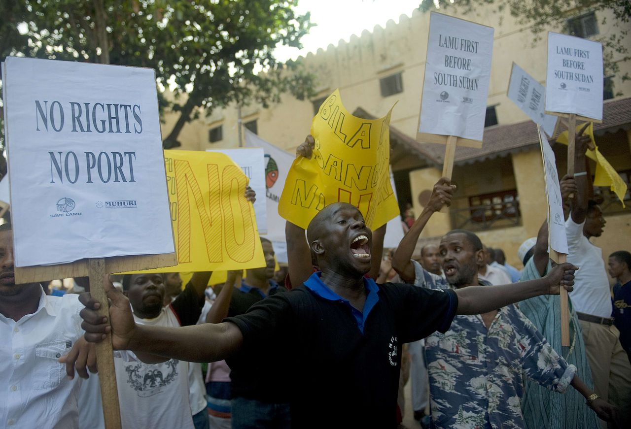 """Residents of Lamu demonstrate on March 1, 2012 against a planned huge port to be constructed near the UNESCO-listed isle, accusing the government of ignoring their concerns. Around 200 placard-bearing protesters gathered at Lamu's town square before marching on the narrow sea front walk-way shouting """"our land, our rights."""" """"We are greatly concerned that the lack of transparency, secrecy and poor accountability in the way the project is being implemented is a dismal reflection of our rights as governed by the constitution,"""" said an activist group in a statement. There are also fears the mega port will impact Lamu town -- whose ancient Swahili architecture is a UN-listed World Heritage site AFP PHOTO/Tony KARUMBA"""