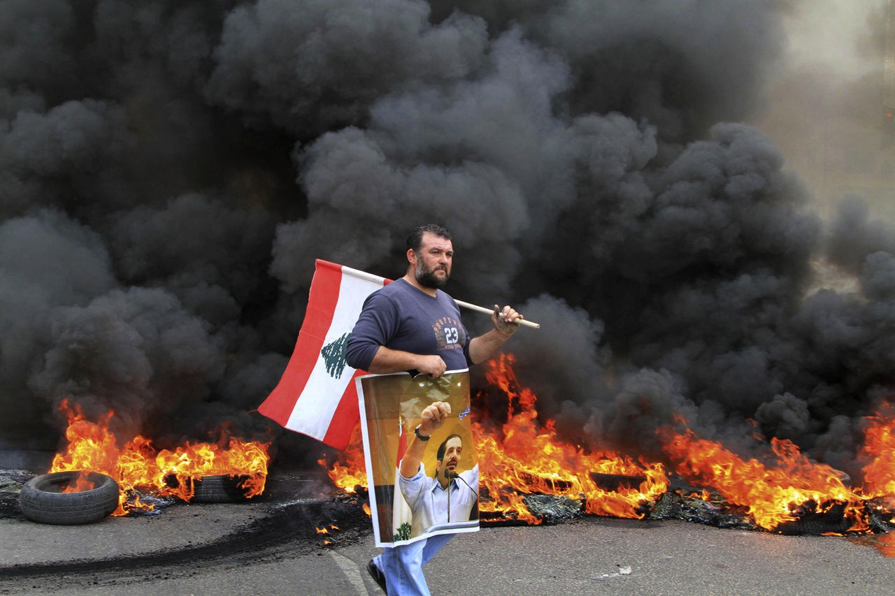 A protester carries a picture of outgoing Prime Minister Saad Hariri and a Lebanese flag as he walks in front of burning tires in the southern port city of Sidon, Lebanon, Tuesday, Jan. 25, 2011. Sunnis protested the rising power of the Shiite militant group Hezbollah on Tuesday, burning tires and torching a van belonging to Al-Jazeera as Lebanese lawmakers gave the militant group's pick for prime minister enough support to form the next government. (AP Photo/Mohammed Zaatari)