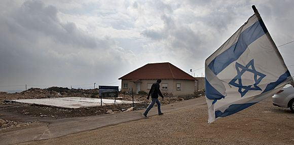 An Israeli flag flies in the wind as a Jewish settler walks past the remaining foundations of a demolished house, in the unauthorized West Bank settlement of Migron, on January 31, 2012 . Israeli premier Benjamin Netanyahu is confident that he will win his Likud party's primaries on January 31, 2012, but a vocal bloc of opponents in Migron, the oldest and largest settlement outpost in the West Bank, accuse the rightwing leader of betraying their cause and are bent on denying Netanyahu universal support. AFP PHOTO/AHMAD GHARABLI