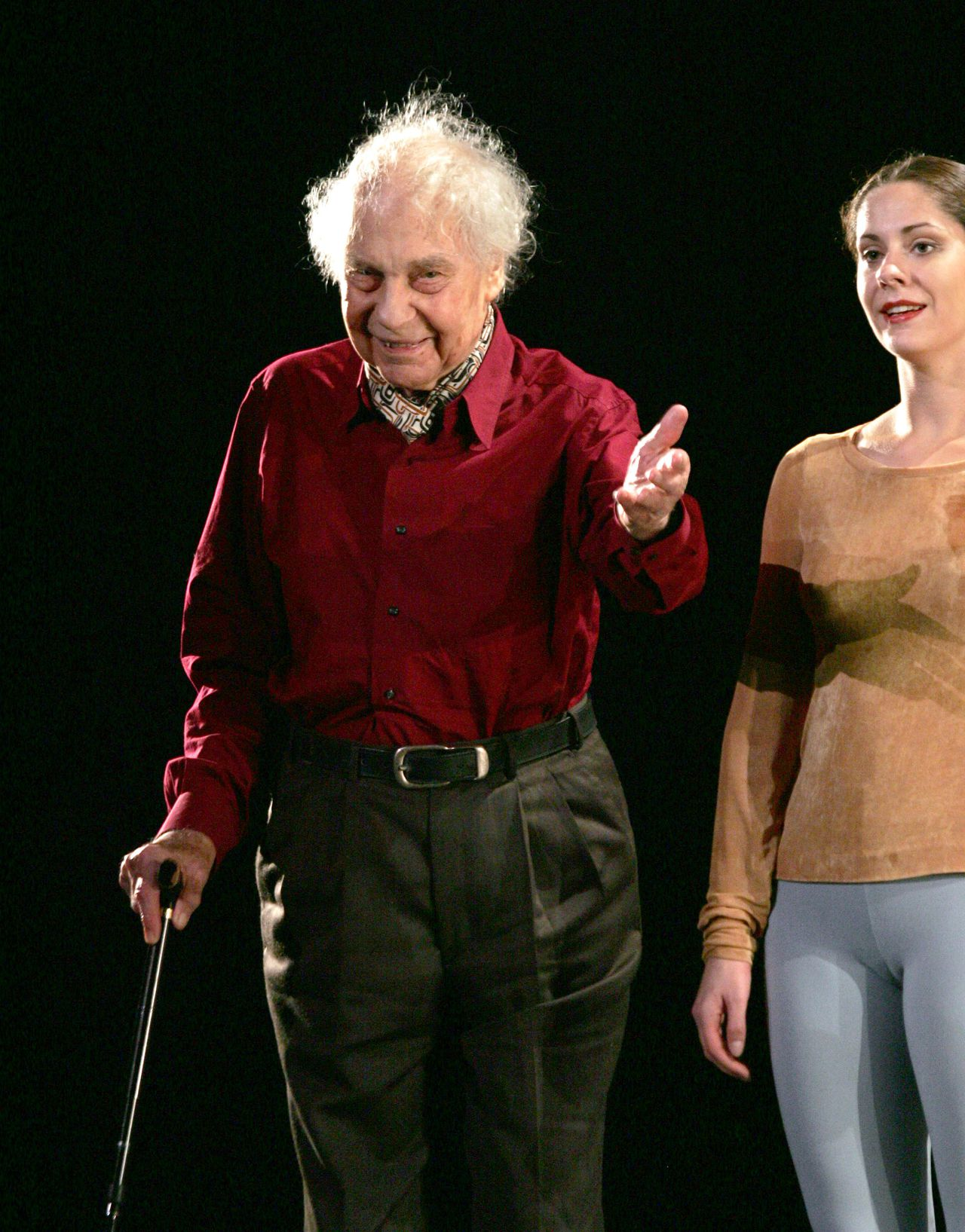 """Cunningham in 2005 op het podium van de Opera in Parijs. Foto AFP (FILES) US choreographer Merce Cunningham salutes the crowd on stage after the presentation of his latest show at Paris' Opera in this January 6, 2005 file photo including a new contemporary dance choreography called """"Views on stage"""". Merce Cunningham, the legendary New York-based choreographer who revolutionized modern dance, has died at age 90, his foundation said July 27, 2009. """"It is with great sorrow that we note the passing of Merce Cunningham, who died peacefully in his home last night of natural causes,"""" the Cunningham Dance Foundation and the Merce Cunningham Dance Company said in a statement. AFP PHOTO/GABRIEL BOUYS"""