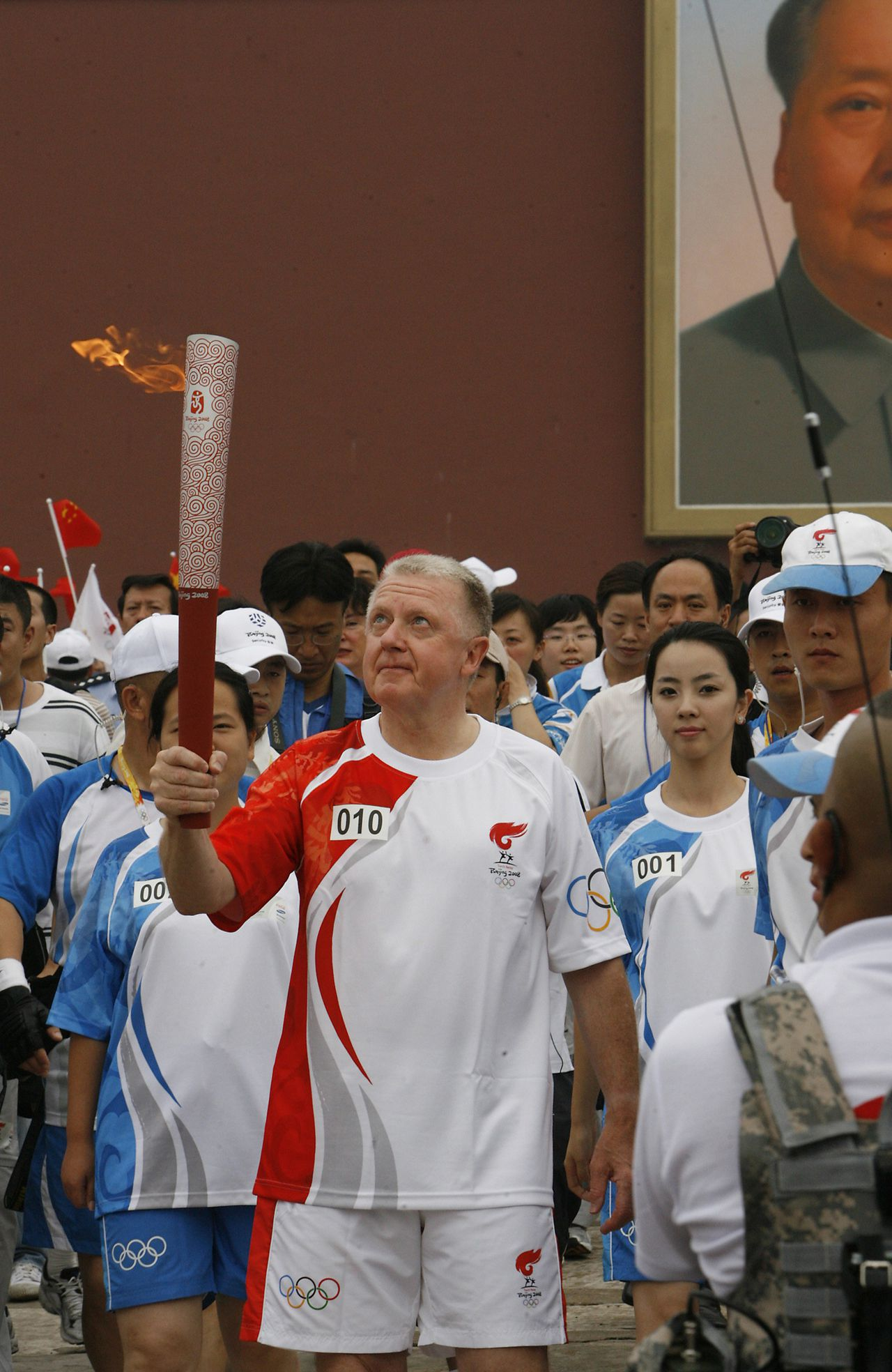 Hein Verbruggen met de olympische fakkel, vlak voor het begin van de Olympische Spelen. Foto Reuters Hein Verbruggen, chairman of the IOC Coordination Commission for the Beijing 2008 Olympic Games carries the torch as he runs through the Tiananmen Gate during the torch relay in Beijing August 6, 2008. REUTERS/Claro Cortes IV (CHINA)