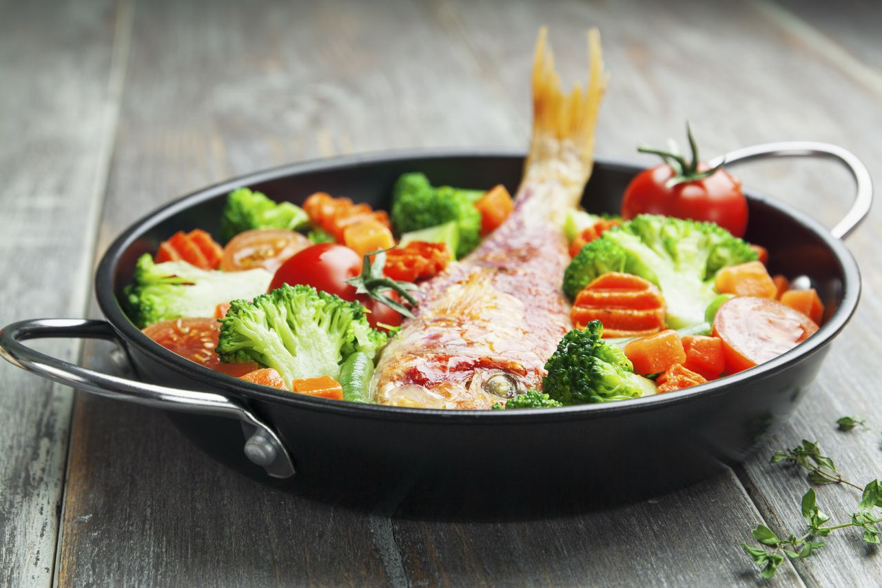 Fried fish with vegetables in the pan