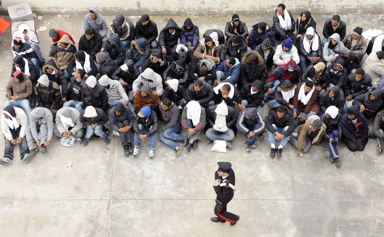 """A Carabinieri police officer walks past migrants as they wait to board a ship towards Porto Empedocle, in Sicily, where they will be taken for document checks, in Lampedusa, Italy, Monday, Feb. 14, 2011. Italy wants to send its police forces to help Tunisia tackle immigration, as thousands of people fleeing the North African nation have reached Italian shores over the past few days. Interior Minister Roberto Maroni said Monday that Italy could send """"our contingents, who can patrol the coasts"""" as well as patrol boats and other equipment, according to the an Italian news agency. More than 4,000 migrants have landed on the tiny island of Lampedusa, fleeing turmoil in Tunisia following street protests and the ouster of longtime president, Zine Al Abidine Ben Ali. (AP Photo/Daniele La Monaca)"""