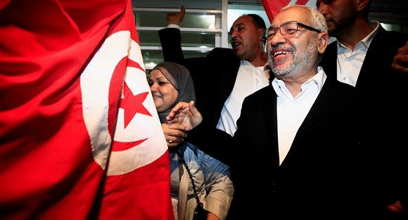 Rachid Ghannouchi (R), leader of the Islamist Ennahda movement, smiles as he meets his supporters after the announcement of the country's election results, outside his headquarters in Tunis October 27, 2011. Tunisian election officials on Thursday confirmed the Islamist Ennahda party as winner of the North African country's election, setting it up to form the first Islamist-led government in the wake of the Arab Spring uprisings. The Ennahda party won 90 seats in the 217-seat assembly. REUTERS/Zohra Bensemra (TUNISIA - Tags: POLITICS ELECTIONS)
