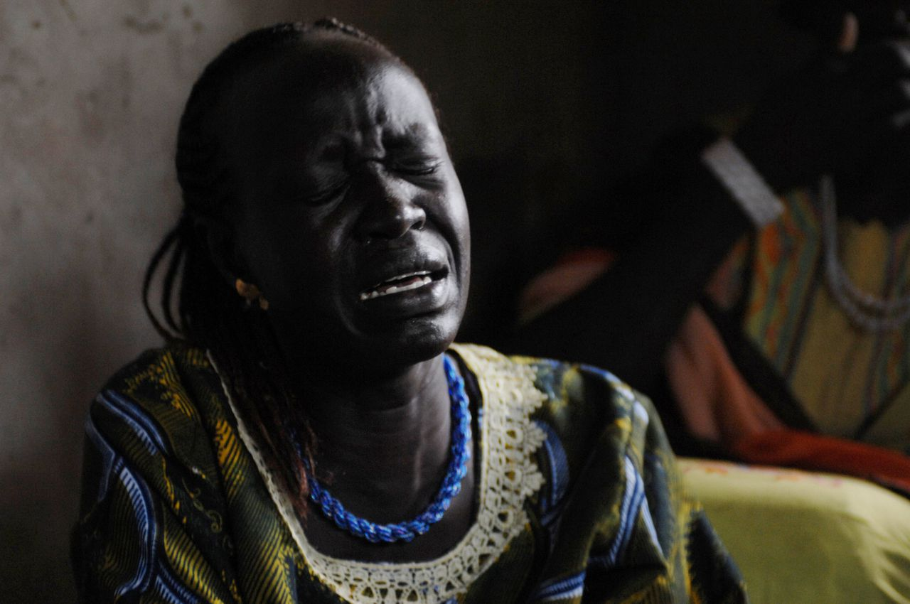 """An unidentified relative of SPLA Major Mabior Mading, who was killed during fighting over the weekend in south Sudan's troubled Jonglei state, mourns during his funeral on September 22, 2009 in his hometown Rumbek, the capital of the state of Lakes. Tribesmen from the Lou Nuer ethnic group raided the Dinka Hol village of Duk Padiet early on September 20, forcing a company of Sudan People's Liberation Army (SPLA) soldiers based there to flee. The African Union has voiced grave concern over the """"atrocious"""" attacks which left more than 100 people dead over the weekend in the Duk County of Jonglei State. AFP PHOTO/HO/UNMIS/TIM MCKULKA -- RESTRICTED TO EDITORIAL USE --"""
