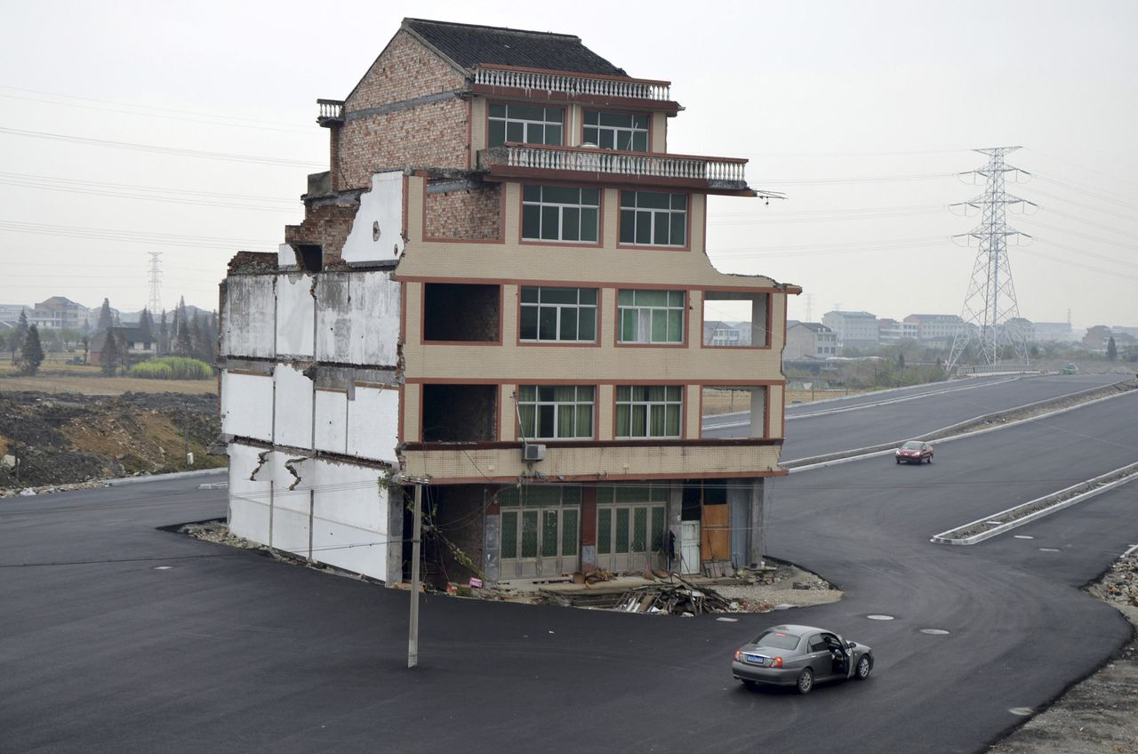 A car stops beside a house in the middle of a newly built road in Wenling, Zhejiang province, November 22, 2012. An elderly couple refused to sign an agreement to allow their house to be demolished. They say that compensation offered is not enough to cover rebuilding costs, according to local media. Their house is the only building left standing on a road which is paved through their village. REUTERS/China Daily (CHINA - Tags: BUSINESS CONSTRUCTION POLITICS SOCIETY TPX IMAGES OF THE DAY) CHINA OUT. NO COMMERCIAL OR EDITORIAL SALES IN CHINA