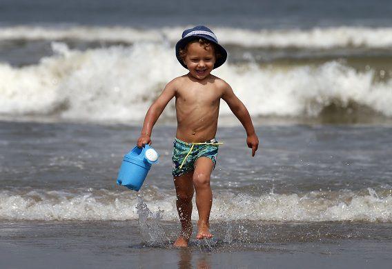 Een jongetje speelt met een gieter tijdens een zomerse dag op het strand van Hoek van Holland.