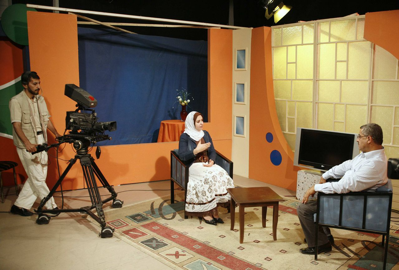 "Presentatrice Sali Abed aan het werk in de televisiestudio van de Palestinian Broadcasting Corporation in Gazastad. Haar moeder belt haar elke dag. 'Ze wil dat ik stop met werken', zegt ze. Foto Reuters Sali Abeid, a Palestinian presenter of programmers (L) during her presentation at Palestine Television in Gaza June 4, 2007. Last week, a group that emerged this year, the Righteous Swords of Islam, threatened to ""slit the throats"" of women presenters on Palestine Television if they do not cover their hair. REUTERS/Suhaib Salem (GAZA)"